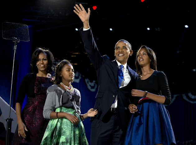 President Barack Obama waves as he walks on stage with first lady Michelle Obama and daughters Malia and Sasha at his election night party Wednesday, Nov. 7, 2012, in Chicago. Obama defeated Republica