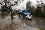 A man tries to remove a car from a flooded road at Elliniko near Athens after a rainstorm Friday, Feb. 22, 2013. Hours of heavy rainfall in Athens caused extensive flooding, inundating basements and forcing authorities to close major roads and a central subway station. The Greek fire brigade says it received more than 900 calls to pump out water in the greater Athens region Friday. (AP Photo/Kostas Tsironis)
