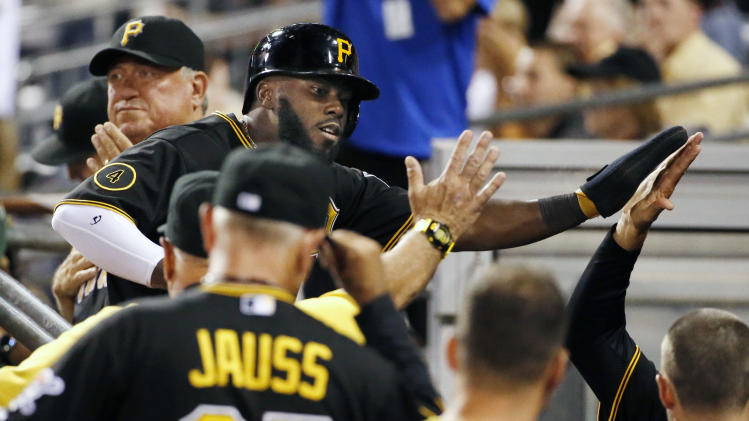 Pittsburgh Pirates' Josh Harrison, top center, returns to the dugout after scoring on a single by Pirates' Jose Tabata off Cincinnati Reds relief pitcher Jonathan Broxton during the eighth inning of a baseball game in Pittsburgh Friday, Aug. 29, 2014. The run proved to be the game winner. The Pirates won 2-1. (AP Photo/Gene J. Puskar)