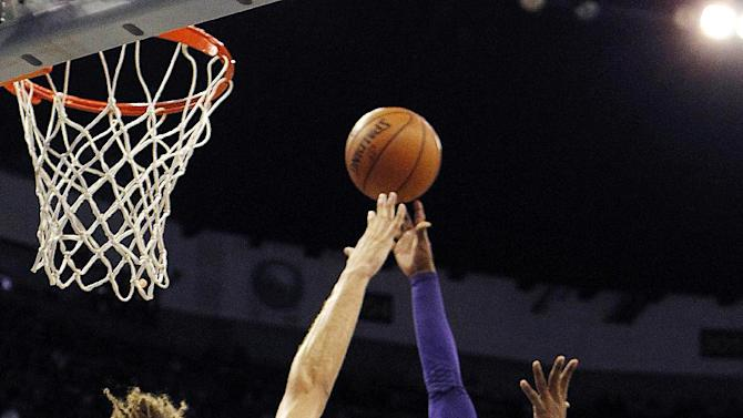Los Angeles Lakers guard Kobe Bryant (24) shoots over New Orleans Hornets center Robin Lopez (15) in the first half of an NBA basketball game in New Orleans, Wednesday, Dec. 5, 2012. With the basket, Bryant became the youngest player in NBA history to break 30,000 points. (AP Photo/Gerald Herbert)