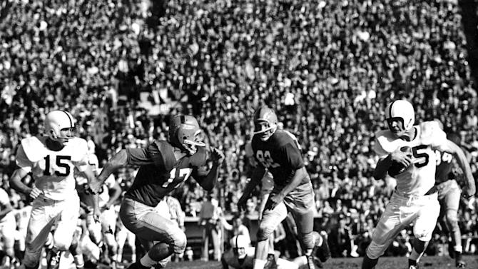 In this photo taken Oct. 27, 1956 and provided by University of Oklahoma Athletics Communications, Oklahoma's Clendon Thomas, right returns an interception as Notre Dame's Jim Morse (17) chases during an NCAA college football game in South Bend, Ind. Notre Dame has had some great victories in its 125 years of playing college football, yet none was as improbable as the 7-0 victory at second-ranked Oklahoma in 1957. That victory ended the Sooners' NCAA-record winning streak at 47 games and came just a season after the Sooners beat the Irish 40-0 in South Bend, still the most lopsided home loss in Notre Dame history. (AP Photo/University of Oklahoma Athletics Communications)