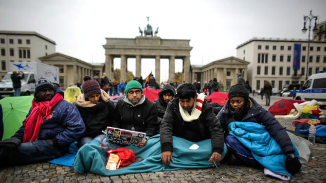 FILE In this Oct. 11, 2013 file picture refugees protest during a hunger strike at the Brandenburg Gate in Berlin, Germany. A rights group has accused the European Union of doing more to secure its borders than to help people fleeing war and dire poverty. Human Rights Watch urged the 28-nation bloc Wednesday Oct. 23, 2013 to focus on preventing tragedies such as this month's drowning of hundreds of migrants making their way from Libya to Italy. The New York-based group says many EU policies claim to be about saving lives but actually attempt to stop people from reaching European shores. (AP Photo/Markus Schreiber,File)