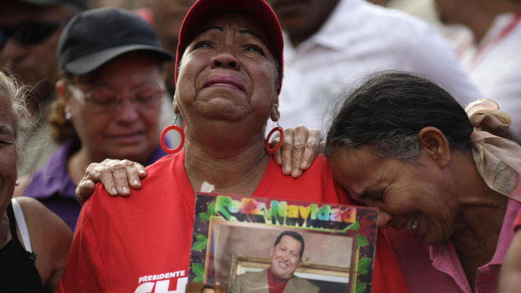 Supporters of Venezuela's President Hugo Chavez cry outside the military hospital where President Hugo Chavez, aged 58, died on Tuesday in Caracas, Venezuela, Wednesday, March 6, 2013.  Seven days of mourning were declared, all school was suspended for the week and friendly heads of state were expected  for an elaborate funeral Friday. (AP Photo/Ariana Cubillos)