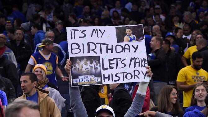 Golden State Warriors fans hold up signs celebrating the Warriors attempt to go 16-0 to start the season on November 24, 2015 in Oakland, California