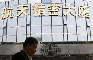Man walks past the logo of China Precision Machinery Import and Export Corp at its headquarters in Beijing