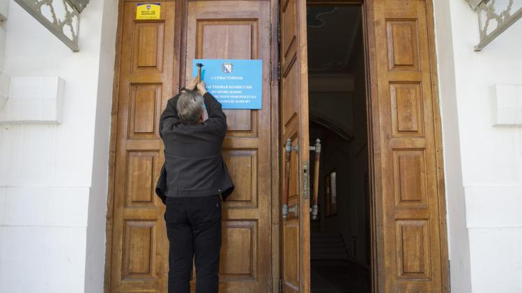 An election commission official installs a sign as he takes part in the preparations for a referendum inside a school in Sevastopol