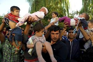 Migrants lift their children during protest in Edirne
