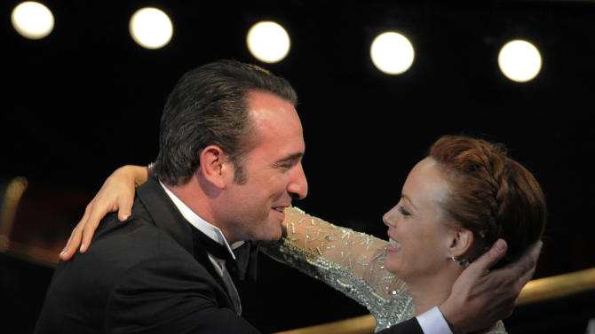"Jean Dujardin is congratulated by Berenice Bejo before accepting the Oscar for best actor in a leading role for ""The Artist"" during the 84th Academy Awards on Sunday, Feb. 26, 2012, in the Hollywood section of Los Angeles. (AP Photo/Mark J. Terrill)"