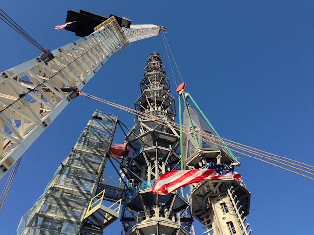 Workers prepare to raise the silver spire atop the 1 World Trade Center building in New York early Friday May 10, 2013. The 408-foot spire will serve as a world-class broadcast antenna. An LED-powered