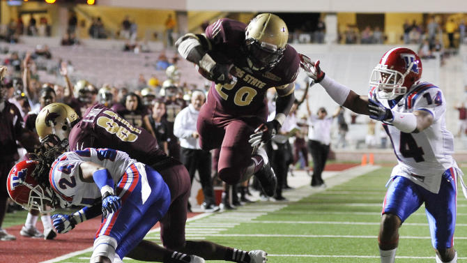 Texas State's Terrence Franks, center, evades Louisiana Tech's Craig Johnson, right, and leaps for a touchdown as Tech's Dave Clark, left, is blocked by Texas' Brandon Smith during the first half of an NCAA college football game, Saturday, Nov. 10, 2012, at Texas State University in San Marcos, Texas. (AP Photo/Darren Abate)