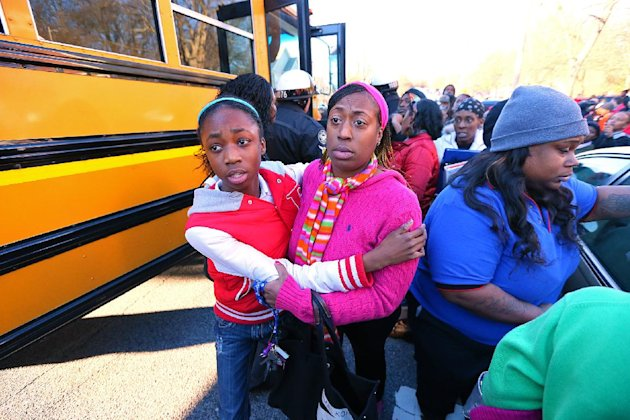 Mother and daughter embrace as Tiffany Myricle, 37, leads her daughter Xavia Denise Myricle away from her school bus when parents and children are reunited at Emmanuel Baptist Church after a shooting
