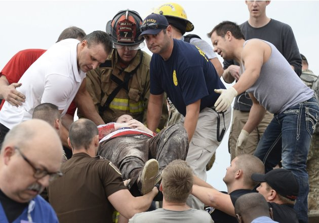 Rescue workers help free one of the 15 people that were trap at a medical building at the Moore hospital complex in Moore