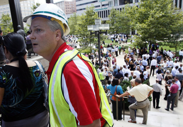 A worker with Baltimore Gas and Electric walks past a square where workers wait for word to re-enter their office buildings after an earthquake was felt in Baltimore on Tuesday, Aug. 23, 2011. Downtown office buildings were cleared and workers were waiting for clearance to re-enter. (AP Photo/Patrick Semansky)