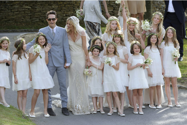 British model Kate Moss and British guitarist Jamie Hince pose for photographers with unidentified bridesmaids, after their wedding in the village of Southrop, England, Friday, July 1, 2011. (AP Photo