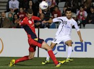 Bunyodkor's Jasur Khasanov (R) crosses the ball past Adelaide United's Daniel Bowles during their AFC Champions League quarter-final football match in Adelaide. The match ended in a 2-2 draw