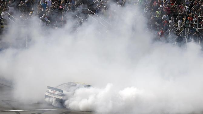 Greg Biffle burns out after winning the NASCAR Sprint Cup Series Quicken Loans 400 auto race at Michigan International Speedway, Sunday, June 16, 2013, in Brooklyn, Mich. (AP Photo/Carlos Osorio)