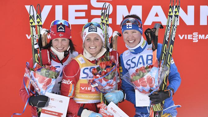 Norway's Therese Johaug, middle, on the winner's stand after the women's FIS World Cup cross country skiathlon race in Falun, Sweden, Saturday, March 15, 2014. To the left runner up Norway's Marit Bjorden and to the right second runner up Finland's Kerttu Niskanen. (AP photo / Anders Wiklund) SWEDEN OUT