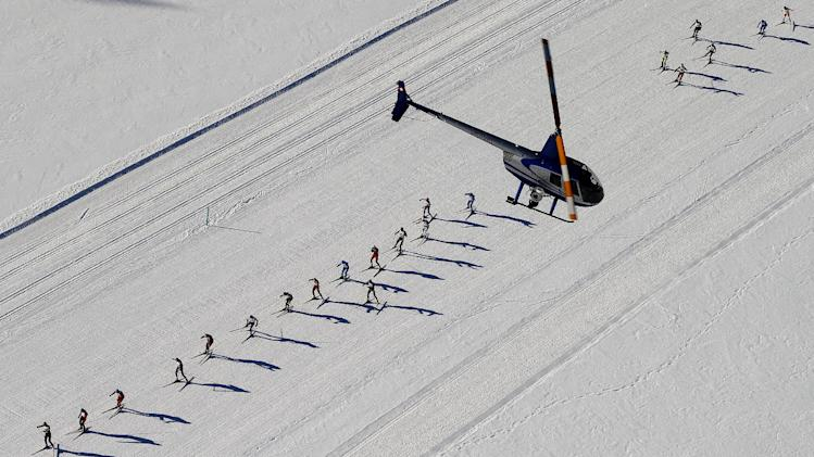 An aerial view shows a helicopter flying cross country skiers racing over the frozen Lake Silsersee during the 46th Engadin Ski Marathon near the village of Maloja