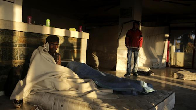 A man from Pakistan sits on a mattress at an abandoned hotel where immigrants have been given shelter, Kos island, Greece, Saturday, May 30, 2015. Greece and Italy are the main points of entry into the European Union for refugees and economic migrants from the Middle East and Africa hoping to reach other European Union countries. (AP Photo/Petros Giannakouris)