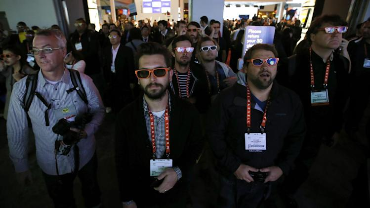 Dylon York, center, and Chase Heavener, right, use 3D glasses to watch a show outside the LG booth at the International Consumer Electronics Show in Las Vegas, Tuesday, Jan. 8, 2013. (AP Photo/Jae C. Hong)