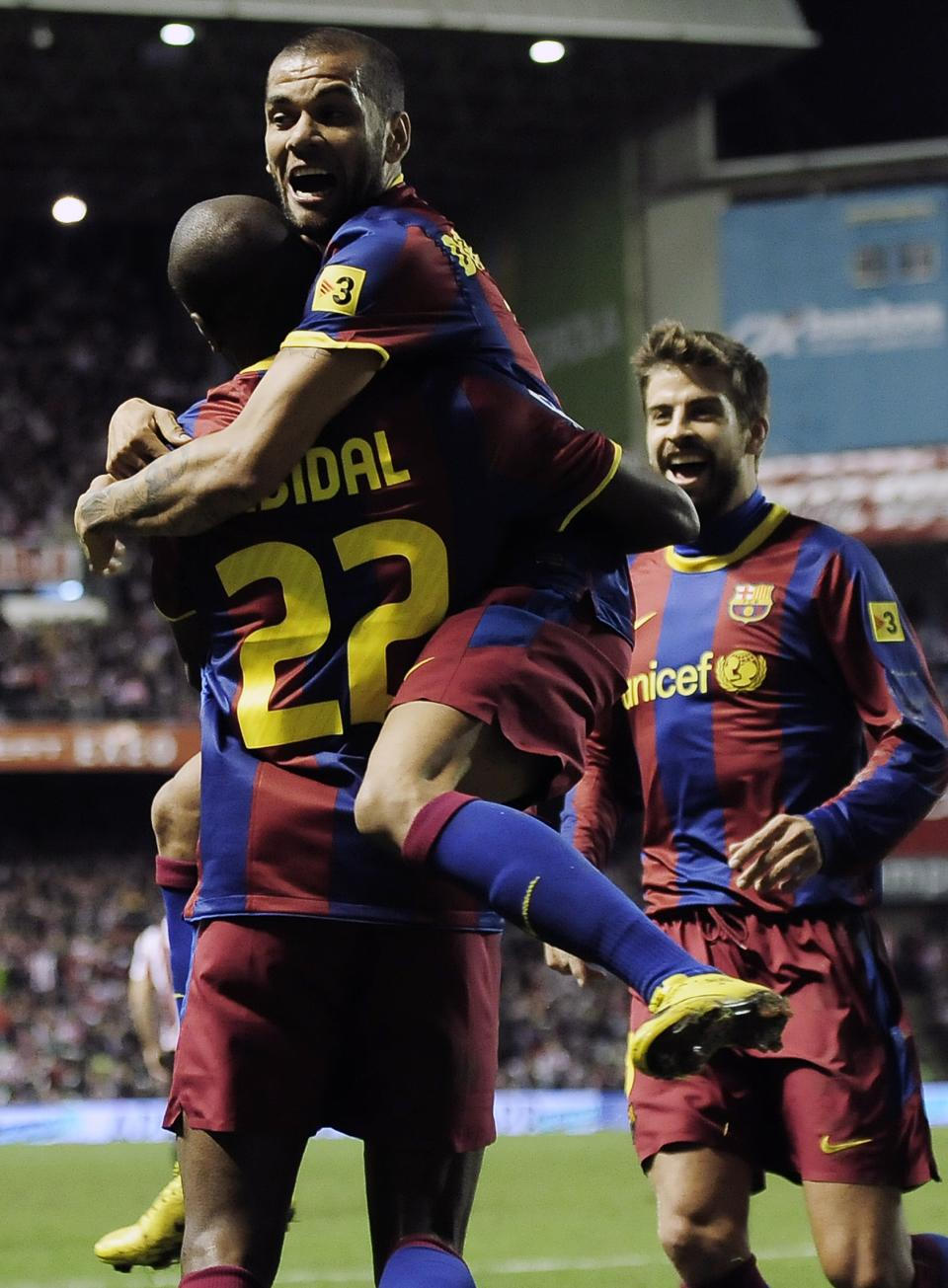 Barcelona's Eric Abidal from France, left, is congratulated by his fellow teammate, Daniel Alves from Brazil, right, after scored against Athletic Bilbao during their Spanish second-leg Copa del Rey soccer match at San Mames stadium in Bilbao northern Spain, Wednesday Jan. 5, 2011. (AP Photo/Alvaro Barrientos)