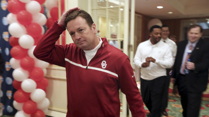 Oklahoma head coach Bob Stoops, left, adjusts his hair as he and Texas A&M head coach Kevin Sumlin arrive for a news conference leading up to the Cotton Bowl NCAA college football game Wednesday, Jan. 2, 2013, in Irving, Texas. Before Sumlin became a successful head coach, he was on Stoops' staff at Oklahoma. Before that, they were both assistant coaches recruiting the same area. Now Sumlin takes his Texas A&M team against Stoops' Sooners in a Jan. 4th Cotton Bowl matchup of former Big 12 rivals that are both 10-2. (AP Photo/LM Otero)