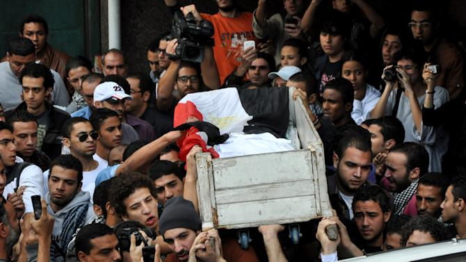 Egyptians carry the body of Gaber Salah, who was who was killed in clashes with security forces during his funeral procession in Cairo, Egypt, Monday, Nov. 26, 2012. Thousands marched through Tahrir square, the birthplace of last year's uprising that toppled authoritarian leader Hosni Mubarak, for the funeral of Salah. (AP Photo/Hussein Tallal)