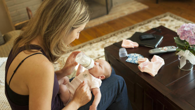 Emily Jordan, left, feeds her six-day old daughter Elle Cynthia Jordan on Wednesday, Sept. 5, 2012 in Naperville, Ill. After Jordan underwent a radical hysterectomy, she and her husband took up an offer from her mother Cindy Reutzel to act as a surrogate for their child. (AP Photo/Sitthixay Ditthavong)