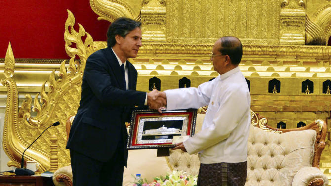 FILE - In this Thursday, May 21, 2015 file photo, Myanmar President Thein Sein, right, shakes hands with U.S. Deputy Secretary of State Antony Blinken as he presents gift during their meeting at Presidential Palace in Naypyitaw, Myanmar. Thein Sein has signed off on a law requiring some mothers to space their children three years apart despite objections by Blinken and rights activists, who worry it could be used not only to repress women, but also religious and ethnic minorities. The Population Control Health Care Bill - drafted under pressure from hard-line Buddhist monks with a staunchly anti-Muslim agenda - was passed by parliamentarians last month. (AP Photo/File)