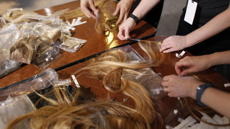 Hair extensions are prepared backstage before the Edun Spring 2013 collection is modeled during Fashion Week, Saturday, Sept. 8, 2012, in New York. (AP Photo/Jason DeCrow)