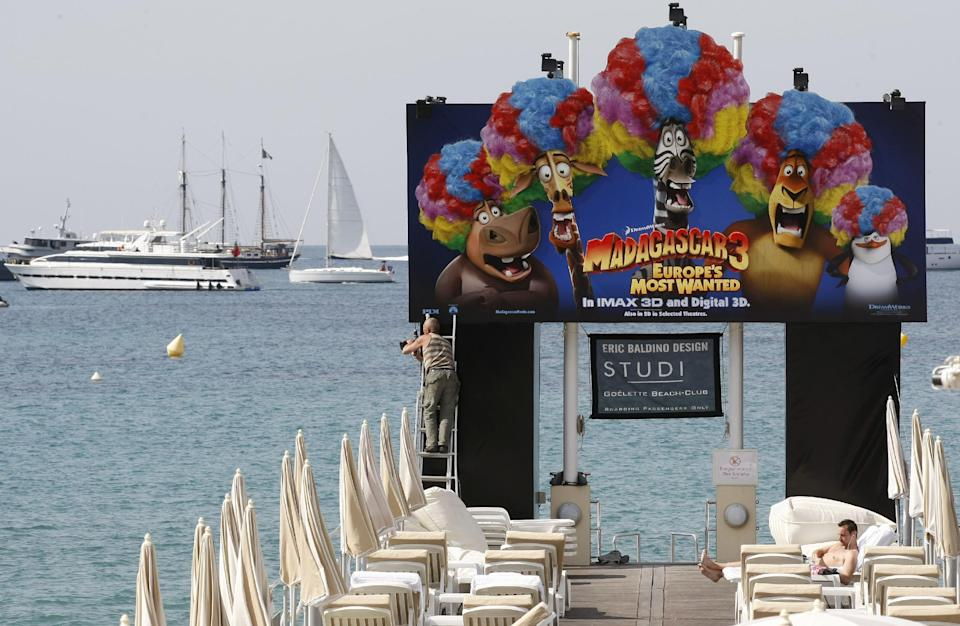 A worker sets up a board advertising Madagascar 3 during final preparations for the 65th international film festival, in Cannes, southern France, Tuesday, May 15, 2012. The Cannes film festival runs from May 16 to May 27, 2012. (AP Photo/Lionel Cirroneau)