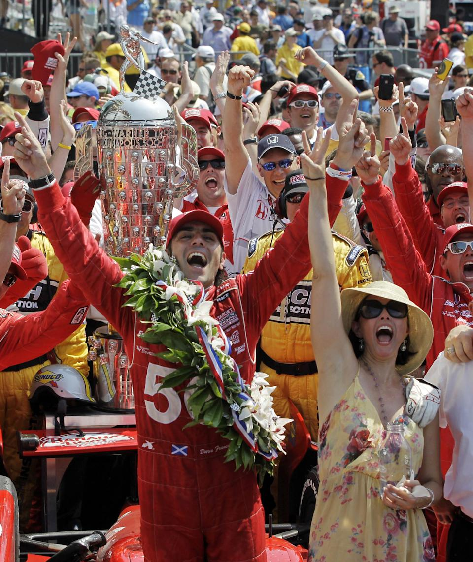 Dario Franchitti, of Scotland, and his wife, actress Ashley Judd, celebrate in victory circle after winning IndyCar's Indianapolis 500 auto race at Indianapolis Motor Speedway in Indianapolis, Sunday, May 27, 2012. (AP Photo/Darron Cummings)
