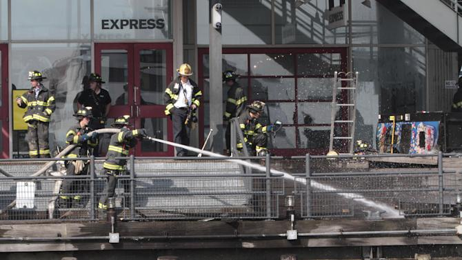 Firefighters work to extinguish a fire at PIer 17 in New York on Saturday, July 14, 2012. Firefighters battled a three-alarm blaze at the South Street Seaport that created a large cloud of smoke over the East River. (AP Photo/Mary Altaffer)