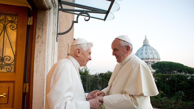 """In this file picture provided by the Vatican newspaper L'Osservatore Romano on Dec. 23, 2013, Pope Emeritus Benedict XVI, left, welcomes Pope Francis as they exchanged Christmas greetings, at the Vatican. It was a holiday at the Vatican and Pope Benedict XVI was speaking in Latin at an arguably boring ceremony announcing new saints, so few people were paying much attention. But what Benedict said a year ago Tuesday changed the course of the 2,000-year-old Catholic Church and paved the way for the historic papacy of Pope Francis. In his soft voice and in a Latin that the cardinals present strained to understand, Benedict announced that he no longer had the """"strength of mind and body"""" to be pope and would retire at the end of the month, the first pope to step down in more than half a millennium. (AP Photo/L'Osservatore Romano, ho)"""