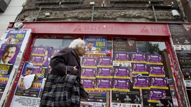A woman walks past a closed-down travel agency plastered with concert posters in Madrid Monday May 21, 2012.  Spain's economy minister de Guindos said the Spanish economy, which has contracted by 0.3 percent in each of the past two quarters, will shrink by about the same amount in the second quarter of 2012. The forecast is for it to decline 1.7 percent for the year. Unemployment stands at a staggering 24.4 percent, and exceeds 50 percent for people under age 25.(AP Photo/Paul White)