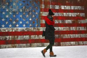A woman walks by a U.S. flag mural on the side of a restaurant during a snow fall in the Williamsburg section of the Brooklyn borough in New York