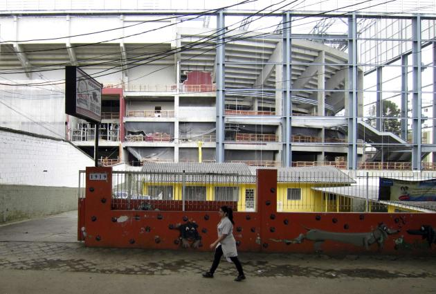 A woman walks past the outside of the Arena da Baixada stadium as work continues in preparation for the 2014 FIFA World Cup soccer championship in Curitiba