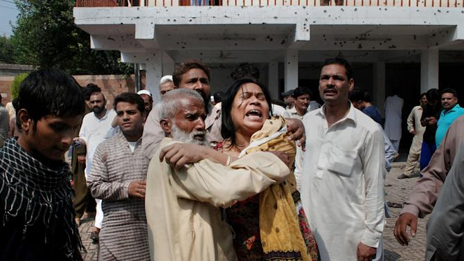 A Pakistani Christian woman mourns over the death of her relatives at the site of a suicide attack on a church in Peshawar, Pakistan, Sunday, Sept. 22, 2013. A suicide bomb attack on a historic church in northwestern Pakistan killed scores of people Sunday, officials said, in one of the worst assaults on the country's Christian minority in years. (AP Photo/Mohammad Sajjad)