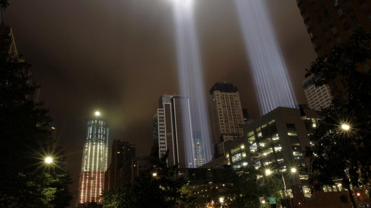 One World Trade Center, left, formerly known as the Freedom Tower, at ground zero is lit up in red, white and blue as two light beams known as The Tribute in Light representing the Twin Towers beam into the sky in Lower Manhattan in honor of the 10th anniversary of the Sept. 11 terrorist attacks, Monday, Sept. 12, 2011, in New York. (AP Photo/Julio Cortez)