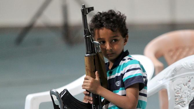 A boy holds a rifle while attending celebrations marking the 25th anniversary of Yemen's unification in Sanaa