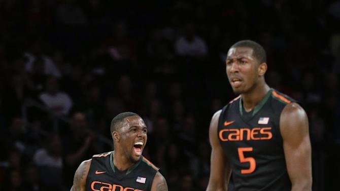 Miami's Ja'Quan Newton (0) and Davon Reed (5) react after a dunk by teammate Sheldon McClellan during the first half of a semifinal against Temple at the NIT college basketball tournament Tuesday, March 31, 2015, in New York, N.Y. (AP Photo/Frank Franklin II)
