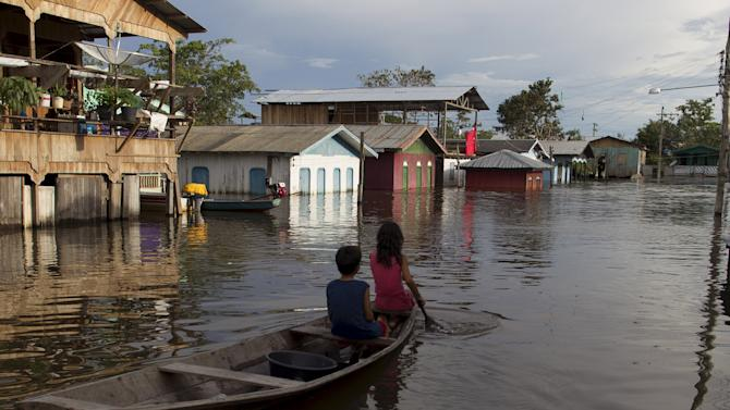 Children paddle their canoe in a street flooded by the rising Rio Solimoes, one of the two main branches of the Amazon River, in Anama
