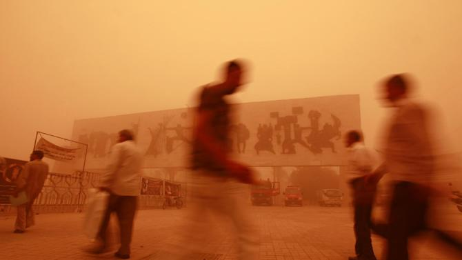 Iraqis walk through Tahrir Square during a heavy sandstorm in Baghdad, Iraq, Tuesday, May 22, 2012. The sandstorm prompted the shutdown of Baghdad's airport on Monday and brought travel complications for envoys trying to reach the Iraqi capital for nuclear talks between Iran and six world powers scheduled to begin Wednesday. (AP Photo/Hadi Mizban)