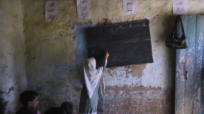 In this Friday, Oct. 12, 2012, photo, a Pakistani student, stands on a chair to the reach the blackboard and write on it, during a class at the EHD foundation school, in Islamabad, Pakistan. A teenage activist recently shot and critically wounded by the Taliban risked her life to attend school, but the threat from the militant group is just one of many obstacles Pakistani girls face in getting an education. Others include rampant poverty, harassment and the government's failure to prioritize education spending.  (AP Photo/Nathalie Bardou)