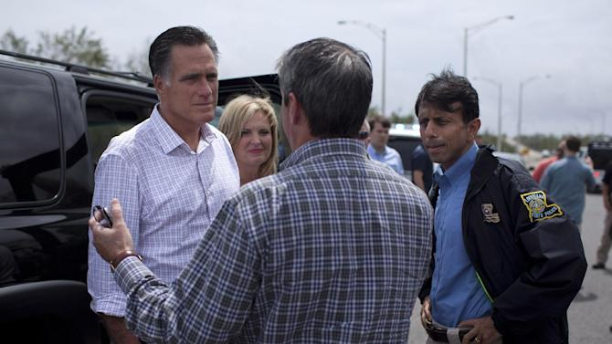 Republican presidential candidate, former Massachusetts Gov. Mitt Romney, his wife Ann, center, and Gov. Bobby Jindal, R-La., right, talk with Sen. David Vitter, R-La., back to camera, during a tour of flooding caused by hurricane Isaac, Friday, Aug. 31, 2012, in Jean Lafitte, La.  (AP Photo/Evan Vucci)