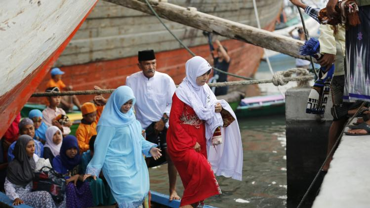 Muslim women disembark from a boat on their way to attend a prayer session on Eid al-Fitr in Jakarta
