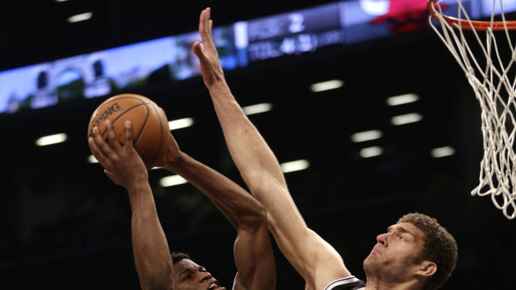 Brooklyn Nets' Brook Lopez, right, blocks a shot by Chicago Bulls' Jimmy Butler during the second quarter of Game 1 in the first round of the NBA basketball playoffs at the Barclays Center, Saturday, April 20, 2013, in New York. (AP Photo/Seth Wenig