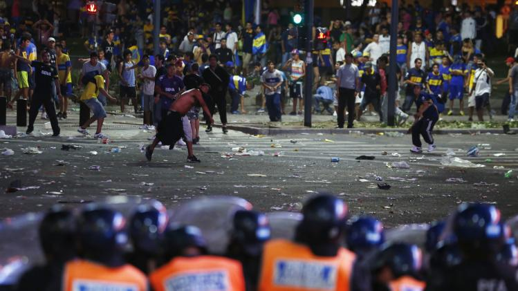 Fans of Argentine soccer team Boca Juniors hurl stones at police after riots broke out during celebrations of Boca Juniors Fan Day in downtown Buenos Aires