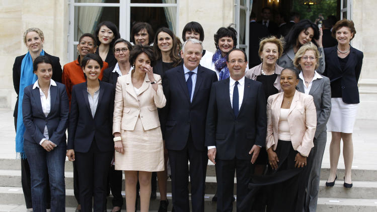 CORRECTS NAME OF PRIME MINISTER TO JEAN-MARC AYRAULT  -- FILE -- In this May, 17, 2012 file photo, French President Francois Hollande, second right, and Prime Minister Jean-Marc Ayrault, center, pose with women of the cabinet after the first weekly cabinet meeting, at the Elysee Palace in Paris. Prime Minister Jean-Marc Ayrault has asked the French equality ministry to set up a series of 45 minute workshops, where politicians are given examples of sexism in daily life and with the aid of slide-shows taught how to avoid sexist stereotypes in political communication. First row from the left: Housing Minister Cecile Duflot, Women's Rights minister Najat Vallaud-Belkacem, Social Affairs Minister Marisol Touraine, Justice Minister Christiane Taubira, right. second row from the left: Deputy Justice Minister delphine Batho, Deputy Education Minister George Pau-Langevin, Sports Minister Valerie Fourneyron, Culture Minister Aurelie Filippeti, Family Affairs Dominique Bertinotti, State Labor Minister Marylise Lebranchu, Environment Minister Nicole Bricq. Top from the left:  Minister for Small Business and the Digital Economy Fleur Pellerin, Deputy minister in charge of French citizen living abroad and French speaking countries Yamina Benguigui , second right, and Elderly People Minister Michele Delaunay. (AP Photo/Michel Euler, File)