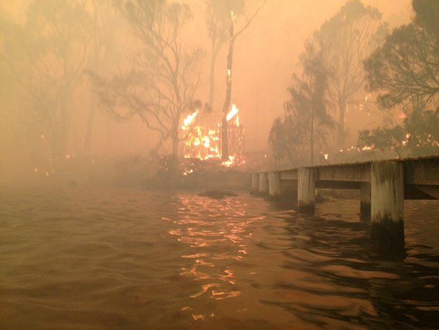 In this Jan. 4, 2013, photo provided by the Holmes family, a building burns near a jetty where Tim and Tammy Holmes attempt to shelter their five grandchildren as a wildfire rages nearby in the Tasman